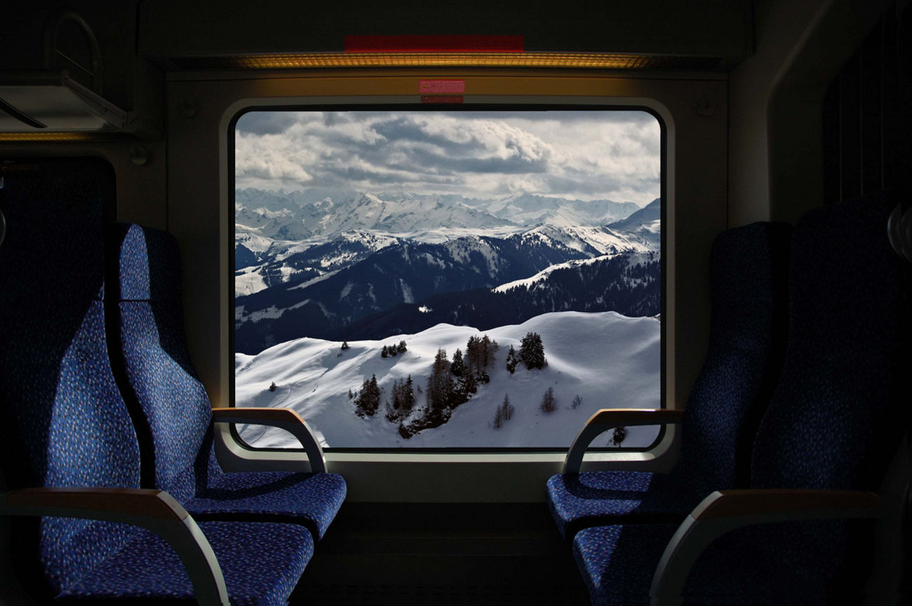 Window of Train and Snow Capped Mountains